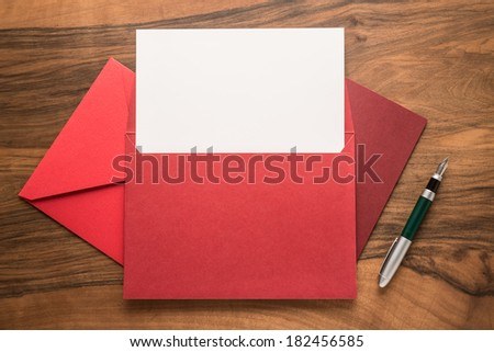 Blank paper, pen and envelopes on wooden background