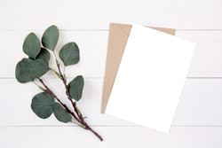 Blank paper sheet copy space with mockup and leaf on wooden table, card, poster and envelope, postcard decoration your design or branding, simplicity and minimal, nobody, flat lay, top view.