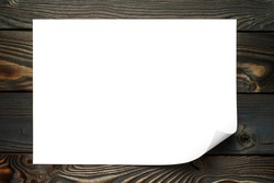 Blank paper sheet with curved corner on dark wooden background