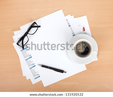 Blank paper with pen, glasses and coffee cup over financial documents