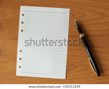 blank paper with pen on wood table