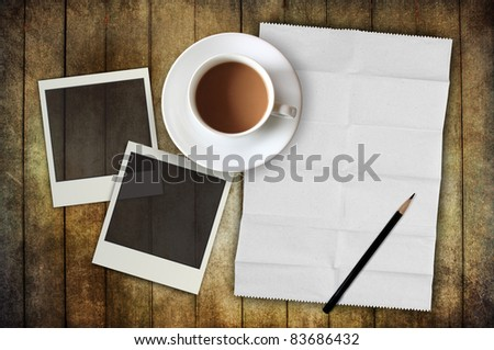 blank paper with photo frame and coffee cup on wooden background