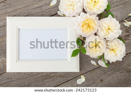 Blank photo frame and white roses over wooden table background