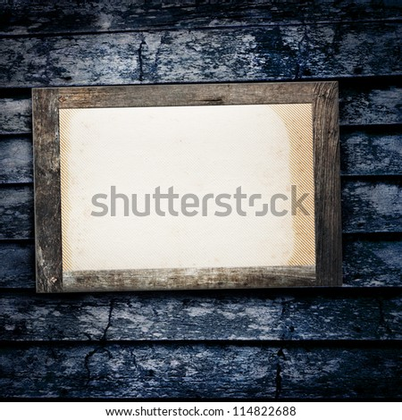 Blank photo frame hanging on old grunge wooden wall
