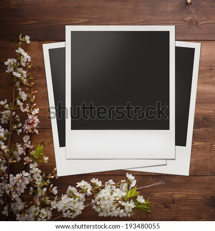 Blank photo frame with summer flowers on wood background for design or montage