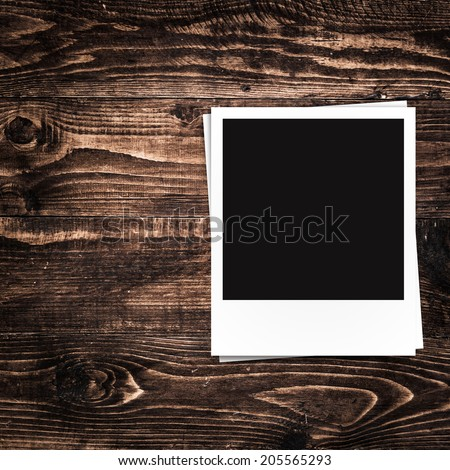 blank photo frames and free space on left side on brown wood texture background