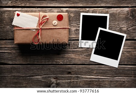 Blank photo frames and vintage gift box (package) with blank gift tag on old wooden background. - stock photo