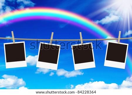 blank photo frames hanging against rainbow sky