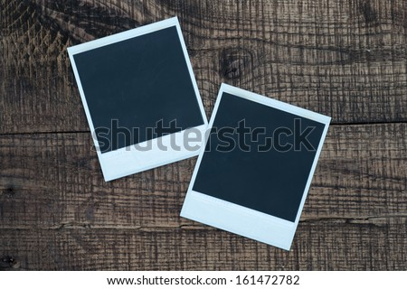 Blank photo frames on a wooden background. Black old pictures.