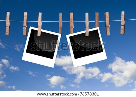 Blank photo frames on line with sky background
