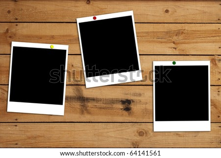 blank photo frames on wooden plank background