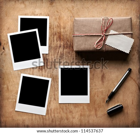 Blank photo frames with vintage gift box and tag on old wooden background.
