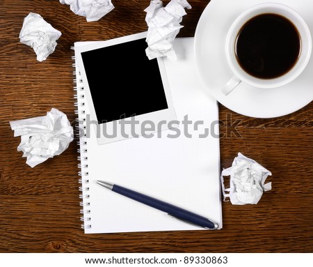 Blank photo on notepad with pen on wooden desk