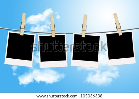 Blank photographs hanging on a clothesline with blue sky background