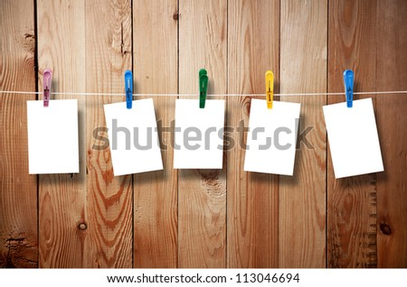 Blank picture frame hanging on clothesline on wood background