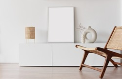 Blank picture frame mockup on white wall. Living room design. Empty white copy space for artwork. View of modern scandinavian style interior with chair. Home staging and minimalism concept