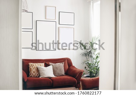 Blank picture frames mockups on white wall. White living room design. View of  modern boho, scandi style interior with sofa, cushions, potted palm plant through open white door. Home staging concept. Stock photo ©