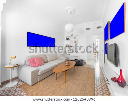 Blank picture template in a cozy stylish bright living room with natural ratan carpet, sofa, wooden table, plants and gallery on wall. Spacious modern interior in earthy colors with frame mockup #1282543996