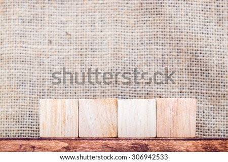 Blank 4 piece of cube wood on wood table and sack fabric wall,mock up for display your content.