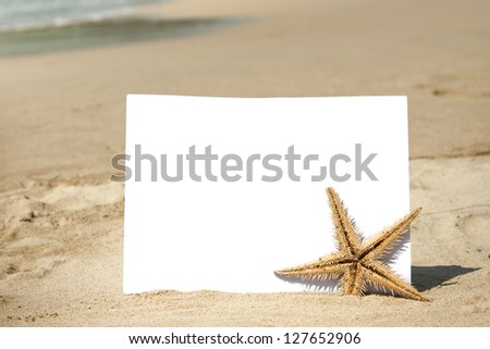Blank piece of paper and starfish on the sand with beach background