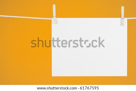 Blank Piece of Paper hanging from a rope with a yellow-gold background