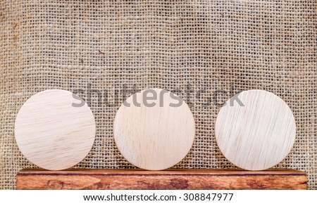 Blank piece of round wood on wood table and sack fabric wall,mock up for display your content.
