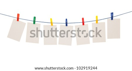 Blank pieces of paper and colored clothespins isolated on white