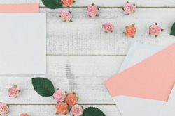 Blank pink card in white envelope decorate with pink rose paper flowers on white wood background with copy space