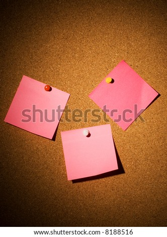 Blank pink papers on a corkboard