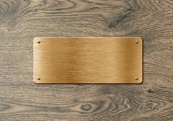Blank polished golden colored name plate on wooden background to ad text, names or logos