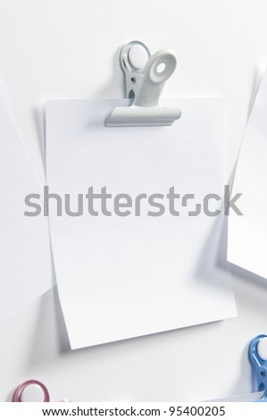 Blank post hanging on the wall with a forceps
