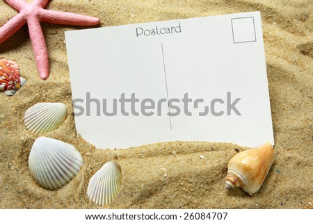 Blank postcard in beach sand, with seashells and a starfish.  Vacation time!