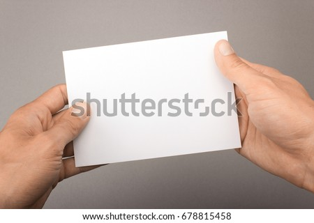 Blank postcard in hands on a gray background. Leaflet A6 mockup #678815458