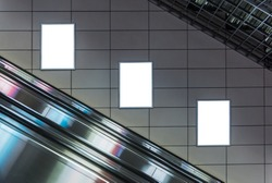 Blank poster mockup in metro station. Three big vertical / portrait orientation blank poster with metro escalator background.