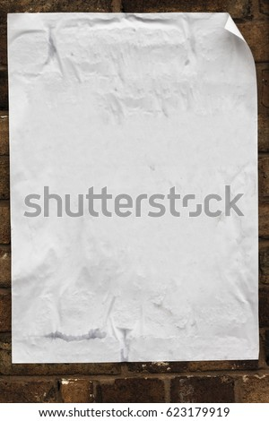 Blank poster texture, crumpled, creased curled at the edges pasted on to a brick wall. #623179919