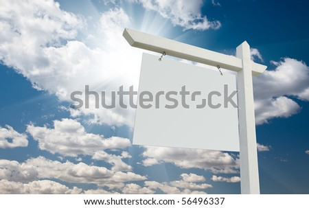 Blank Real Estate Sign over Clouds and Blue Sky with Sun Rays.