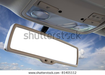 Blank rear view mirror against blue sky.