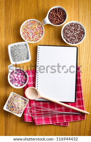 Blank recipe book with a variety of candy sprinkles.