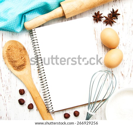 blank recipe book with baking ingredients on a old wooden background