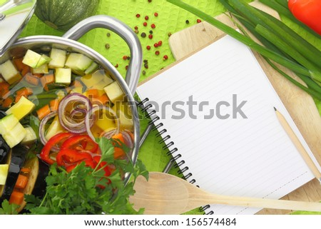 Blank recipe book with vegetable soup, kitchen equipment and veggies around them