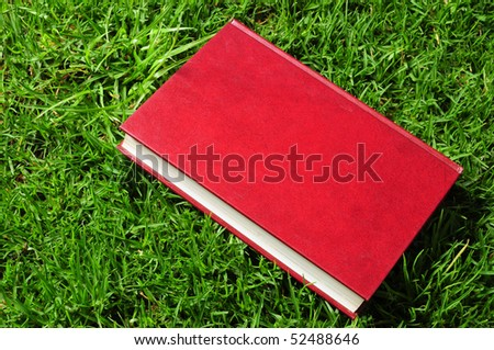 Blank red book on grass.