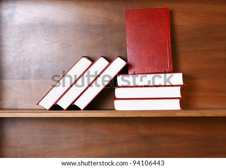 blank red books on wood bookshelf with copy space in natural light