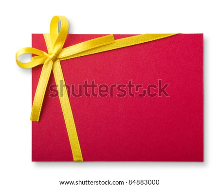Blank red gift tag tied with a bow of gold satin ribbon. Isolated on white, with soft shadow
