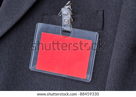 Blank red ID card with copy space on the men's suit - stock photo
