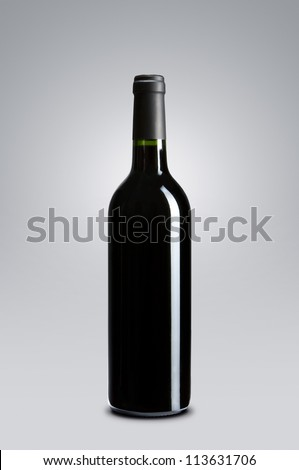 Blank red wine bottle over gray background with copy space