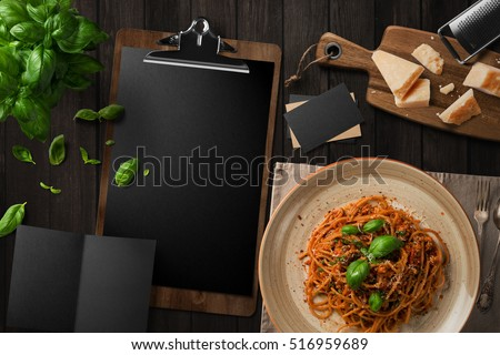 Blank restaurant menu template on dark wood table, with pasta, basil cheese, top view.