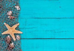Blank rustic antique teal blue aged wooden sign background with fish net border, seashells and one gold starfish; beach sign with painted copy space