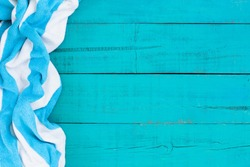Blank rustic teal blue wood beach sign with turquoise and white striped beach towel border; blue painted background with copy space