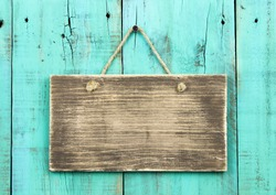 Blank rustic wooden sign hanging on washed out teal blue distressed antique wood background; color copy space