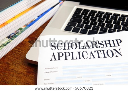 blank scholarship  application on desktop with books and laptop - stock photo